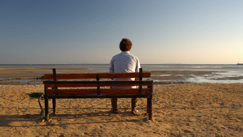 young man sitting    bench   beach stock