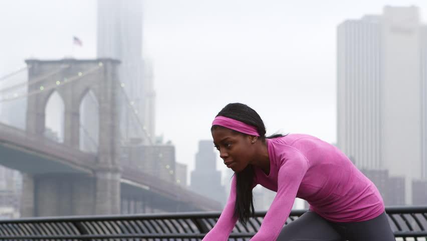 A woman gets ready to take a run in Brooklyn Bridge park in the rain | Shutterstock HD Video #6016151