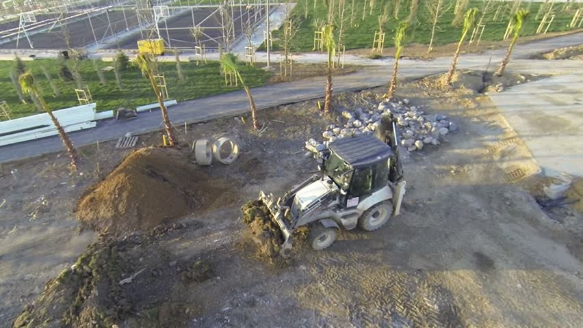 Excavator moving sand soil at construction area view from aerial camera. Wheel excavator bulldozer tractor working at construction site. Construction Heavy Equipment.