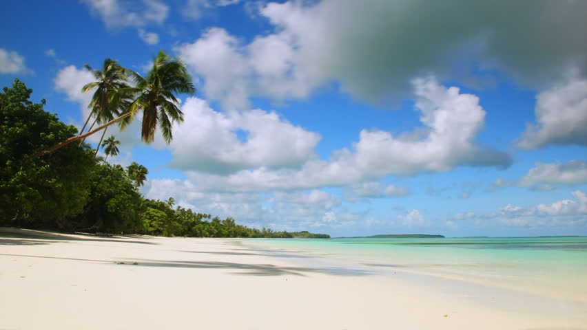 Time-lapse of white sand tropical beach with turquoise water, coconut trees swaying in the wind and clouds passing by. - HD stock video clip