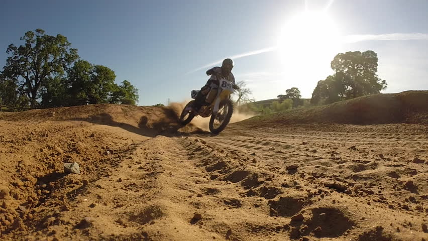 MOTOCROSS MOTORCYCLE RIDER IN BACK-LITE LIGHT AT SUNSET THROWS DUST IN AIR WHILE IN EXTREME SLOW MOTION  HIGH DEFINITION STOCK VIDEO FOOTAGE HD | Shutterstock HD Video #6043196