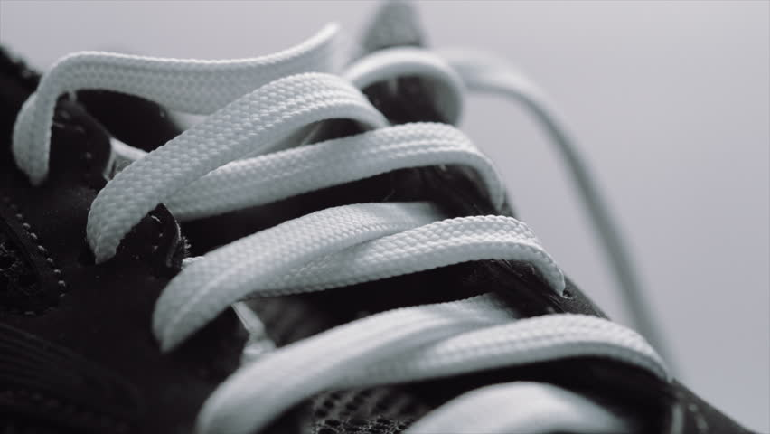 Trainer shoe or sneaker close up UHD stock footage. A close up dolly shot of a training shoe or sneaker set against a white backdrop.