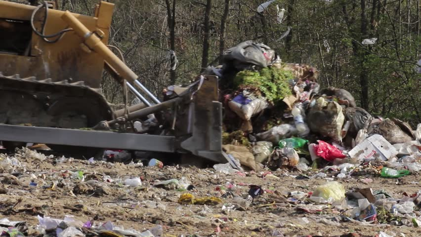 16/35 Bulldozer (tractor) pushes a pile of trash at landfill. Vehicle flattening garbage to waste.Bulldozer moves non biodegradable garbage at the dump.Truck working on dump.Footage available in 25fps - HD stock video clip