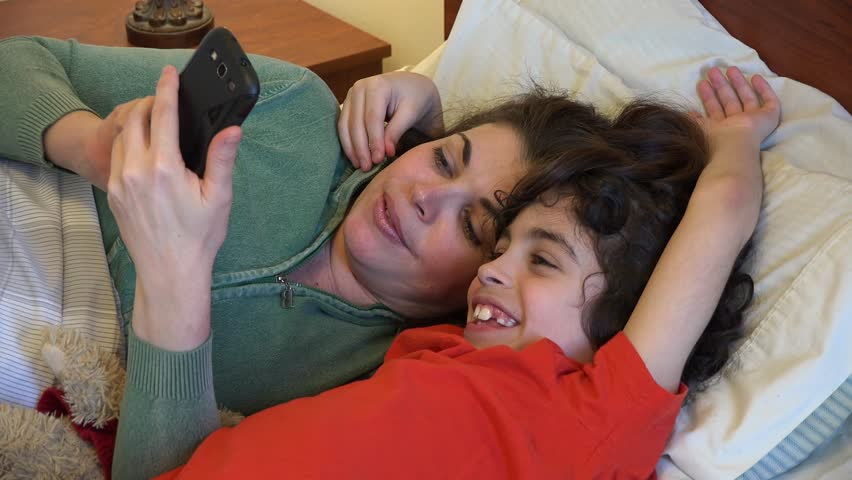 Single mother and son having fun while checking internet in a smartphone before going to bed.