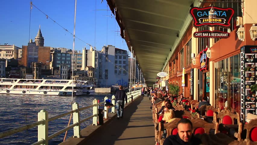 ISTANBUL - MARCH 31, 2014: People relax in the restaurants of Galata Bridge with the Galata Tower seen in the distance.The Bridge spans the Golden Horn and has pubs and fish restaurants on first floor