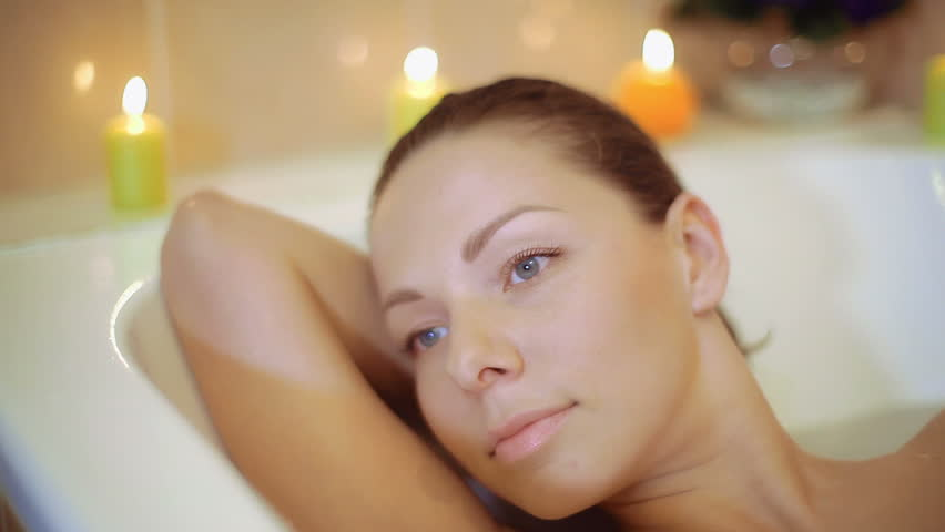 Young, attractive woman is lying in the bath, it looks very comfortable and happy