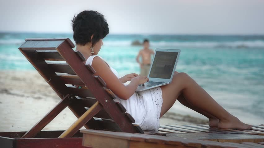 Hispanic female in white dress working on laptop in a beach chair on mexican caribbean
