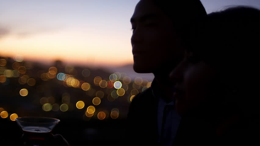 Close up of a man and woman standing on a roof drinking a cocktail at sunset with the city lights behind them