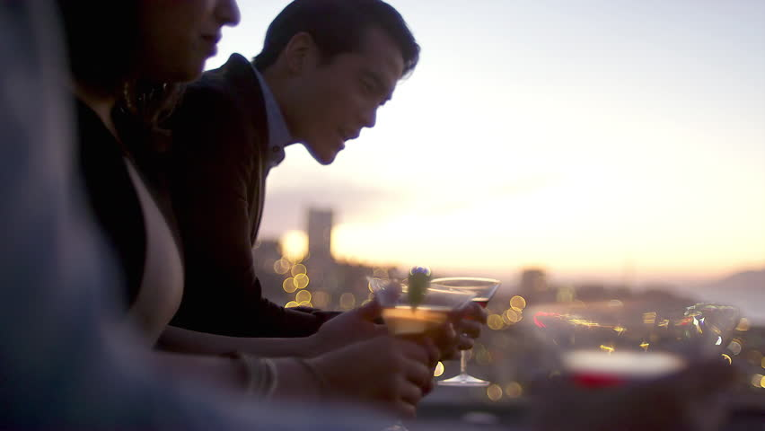 Friends hang out and drink cocktails on a rooftop bar at sunset in San Francisco