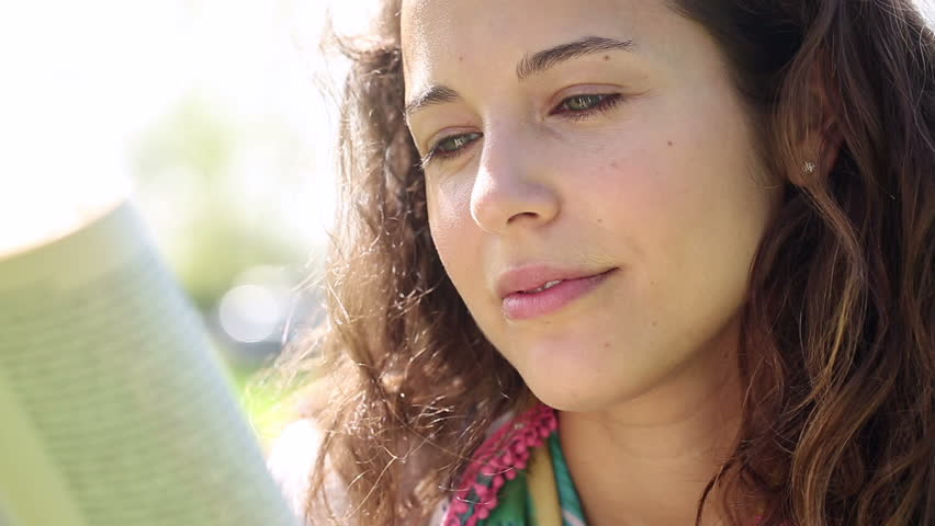 Close up of an attractive young woman reading a book whilst outdoors on a sunny day | Shutterstock HD Video #6079439