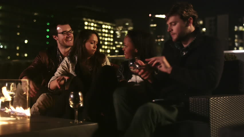 A group of friends have drinks on a rooftop bar at night and take pictures of each other - 4K stock footage clip