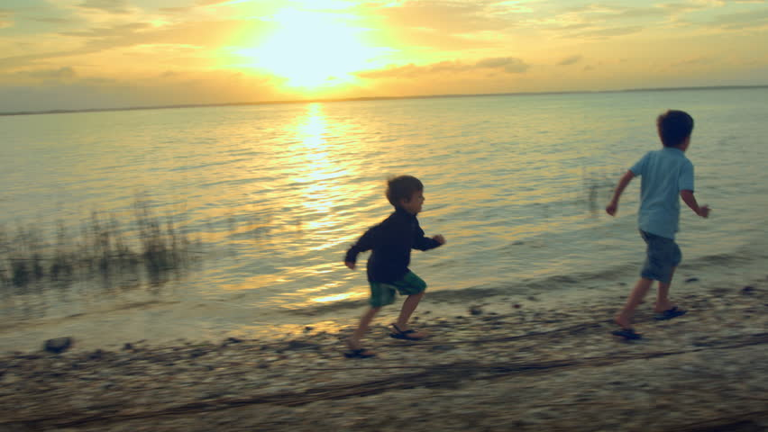 Two little boys running on the shore of a peaceful lake at sunset. 4k Footage - 4K stock video clip