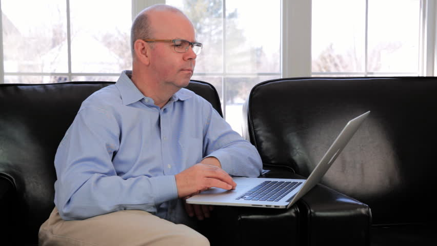 Mature Baby Boomer Caucasian Man Sitting Using A Laptop To Surf The Internet Sat At Home In A Leather Chair