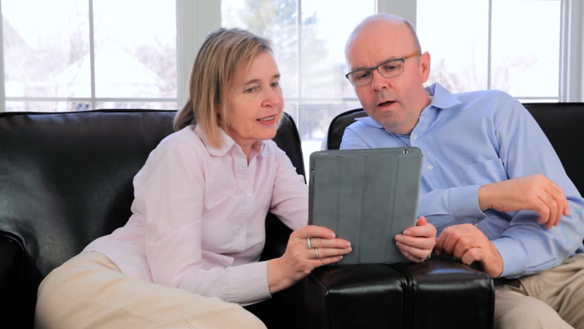 Happy Mature Married Couple Using A Tablet Computer To Surf The Internet