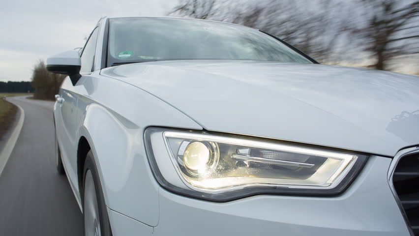 BAVARIA - DEC 2013: Audi A3, 2013 model, driving through forest. On board shot of front right side.  Headlights on. HD, Apple ProRes, 422 HQ