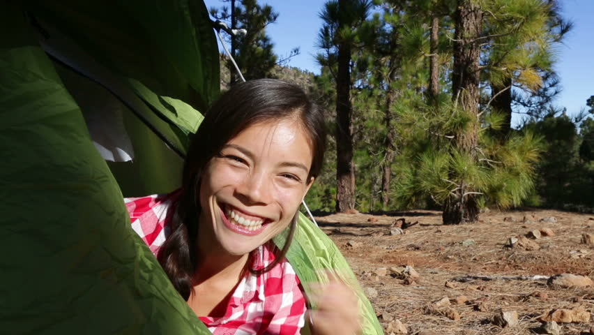 Camping woman waving hello from tent smiling happy outdoors in forest. Happy girl saying hello and good morning opening tent. Smiling mixed race Asian Caucasian girl saying hi looking at camera.