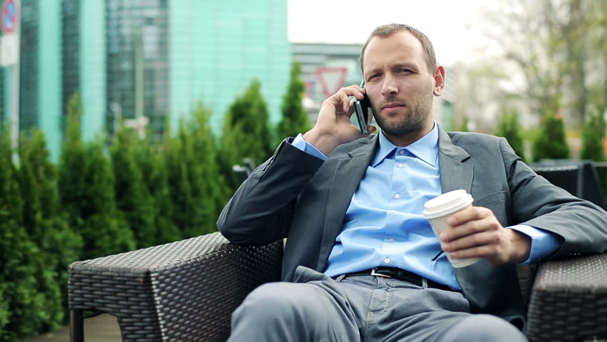 Young businessman talking on cellphone, drinking coffee in cafe
