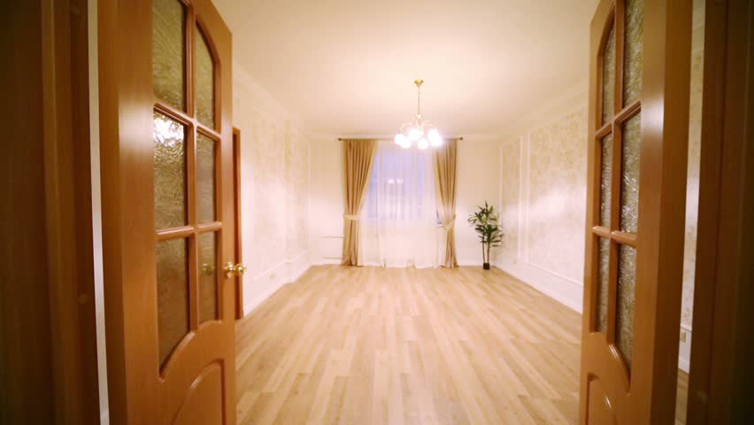 Opening wooden doors to a small empty room in a new apartment