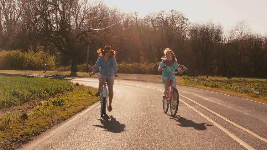 Two Friends Enjoy A Bike Ride Together In The Countryside