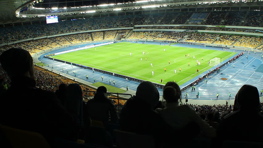 Fan drinking alcohol during football match stadium arena evening. People watching soccer tournament from tribunes. Men disappointed with team's attack on illuminated green field. Supporters' emotions