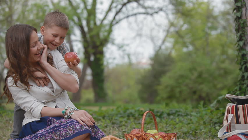 little boy 6 years gives mom apple. They rest in the park on a picnic, mom says on the phone, and her son playing outdoors