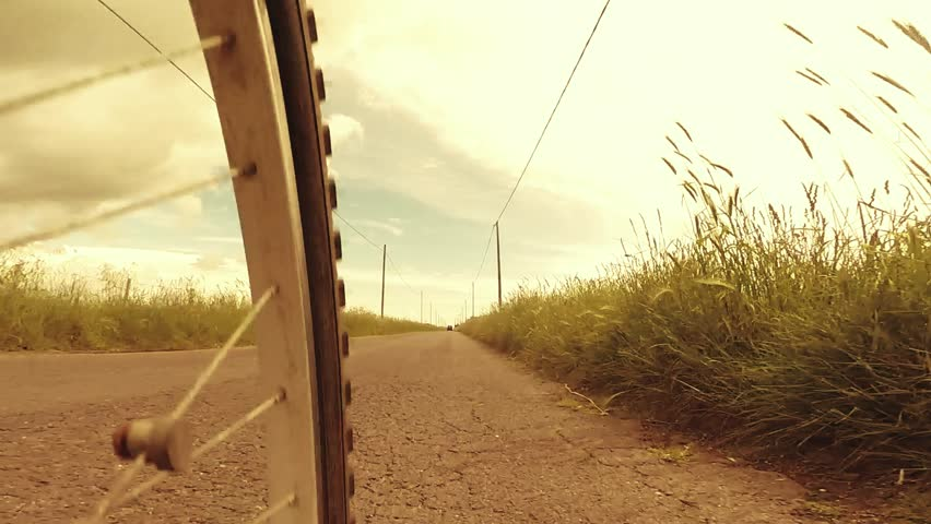 Low angle view shot of riding a bicycle on country road along green fields, retro revival style footage.