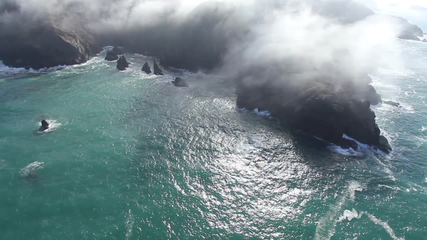 Aerial fly over of the fog over a rocky coastline