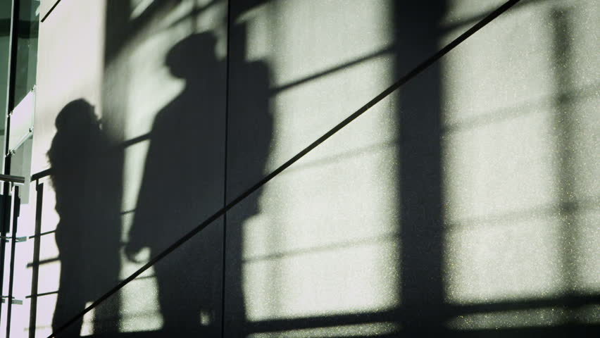 Shadow of businessman & businesswoman shaking hands in modern city building - HD stock video clip
