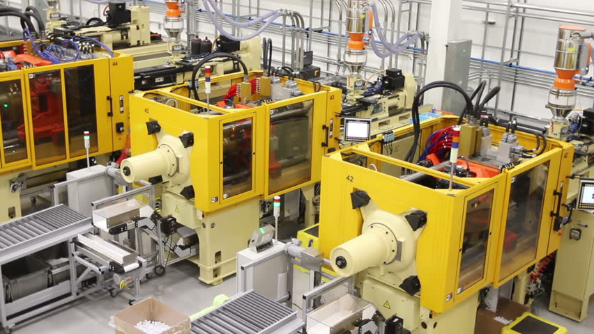 Close up of the mold of an injection molding machine making plastic parts in a factory