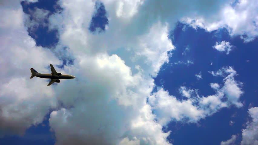 Airplane taking off, side view; blue sky, white clouds