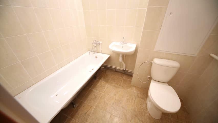 Full bathroom with bath, pedestal washbasin, toilet bowl, towel dryer.
