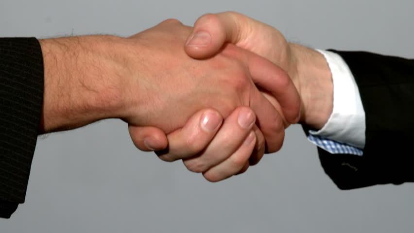 Men shaking hands on grey background in slow motion