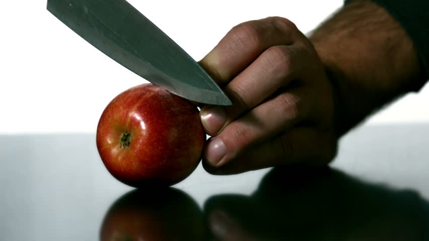 Man slicing apple with large knife in slow motion