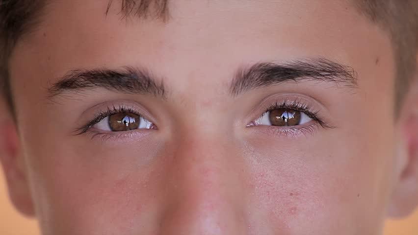 Cute caucasian teenager looking at camera. Eyes close up - HD stock video clip