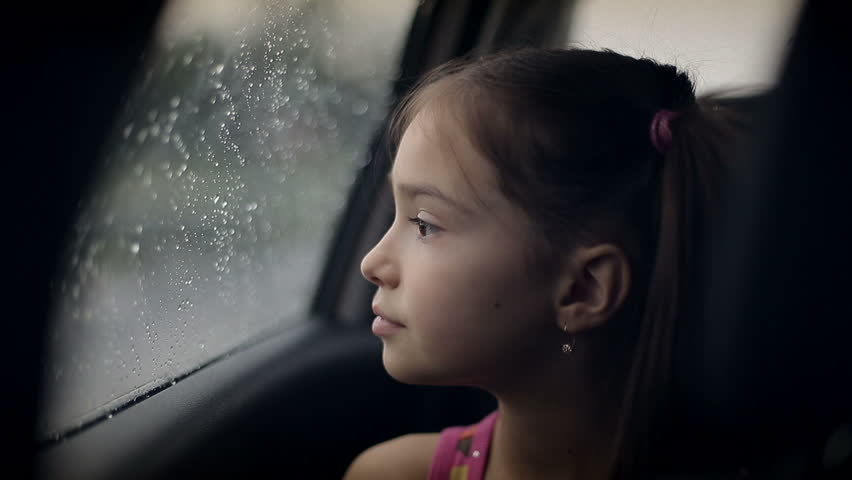 little girl looking out from car window rainy weather