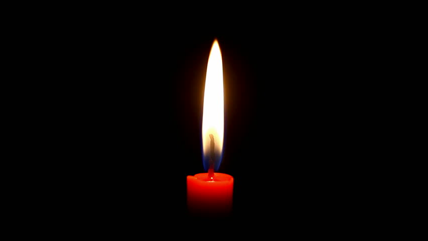 a candle is burning on dark