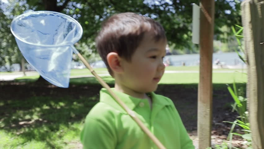 Little Asian Boy Walks On A Path Through A Park With A Butterfly Net Over His Shoulder - HD stock video clip