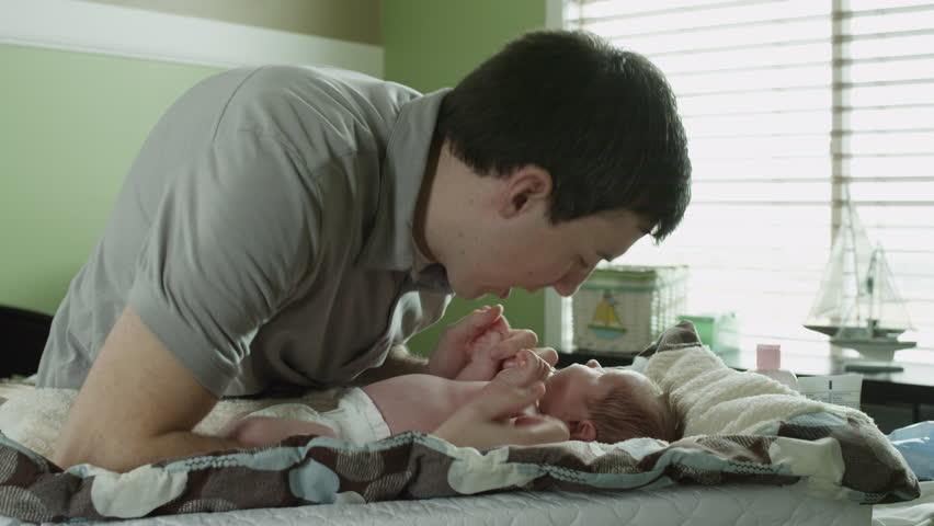 Medium Shot Father changing baby boy's diaper in nursery