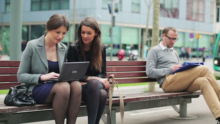 Businesspeople working on street bench in the city and talking