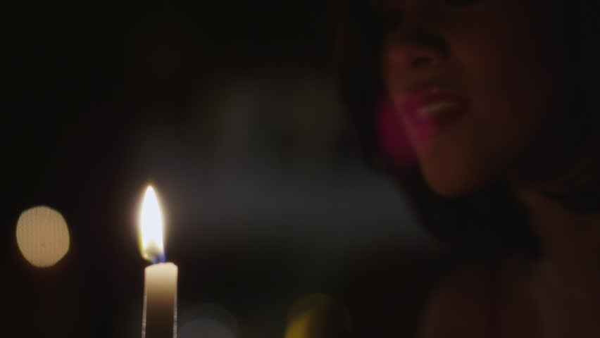 Close up shot of woman blowing out candle flame