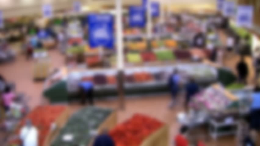 Supermarket. Real time. Defocused shot of modern supermarket. Shoppers in the fruit and vegetable section. Real time shot. Great background to overlay a graphic, logo, or text bar.  - HD stock video clip