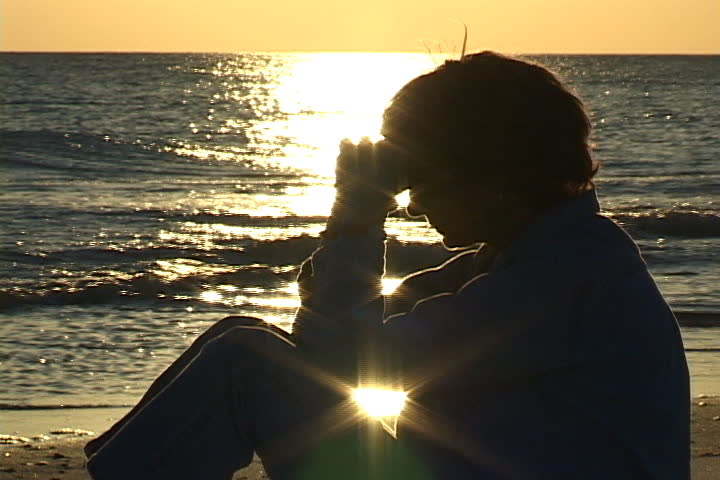 Mature woman sits on the beach praying with hands folded against head. Sunlight sparkles on the water in the background. Shot on miniDV from a tripod. - SD stock video clip