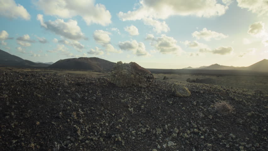 Sunset time-lapse of a volcanic desert on the Canary Island of Lanzarote. Rocks and stones in the foreground as the shot slides to the right to reveal the sparseness of the desert.