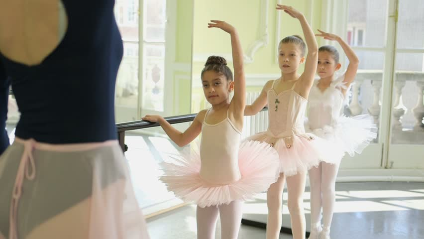 Female Ballet Dancer stands before a trio of young Ballerinas demonstrating the movements and encouraging leg and arm extension