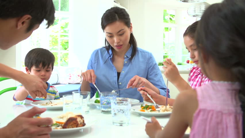 Asian Family Sitting At Table Eating Meal Together Stock