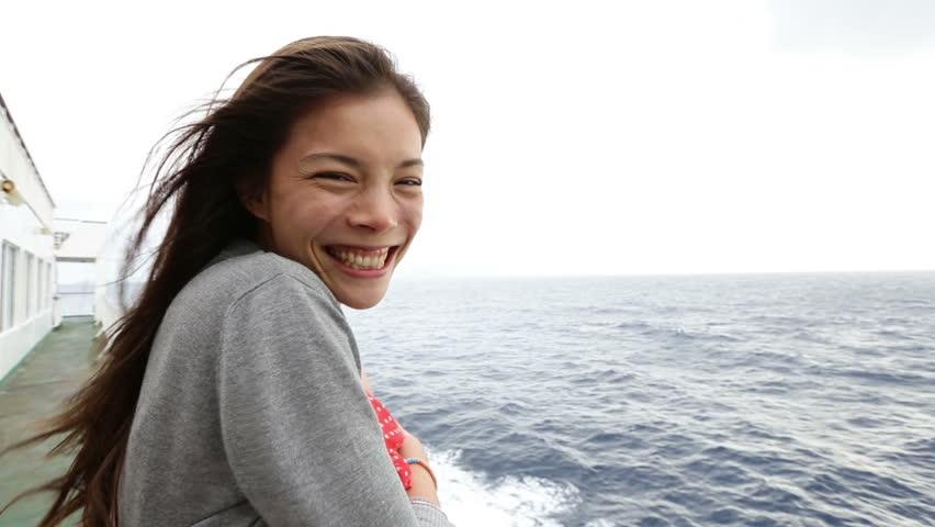 Cruise ship woman on boat Cruise ship woman on boat waving hand saying hello smiling looking at camera. Young woman traveling on vacation travel sailing on sea ocean. Mixed race Asian Caucasian woman.