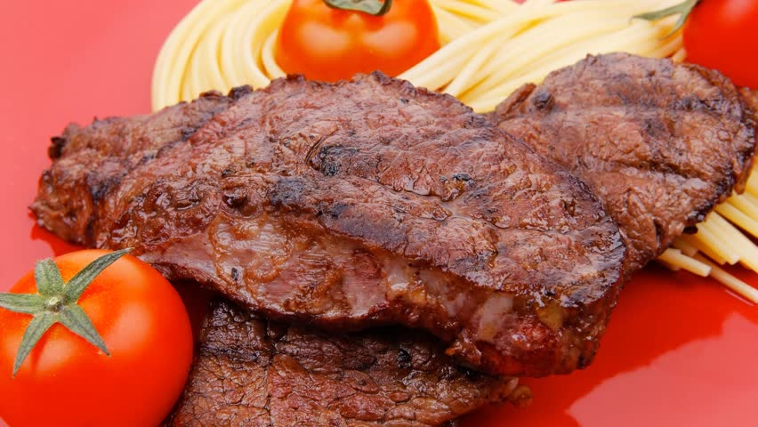 meat grilled beef steak with pasta and tomatoes on red plate 1920x1080 intro motion slow hidef hd