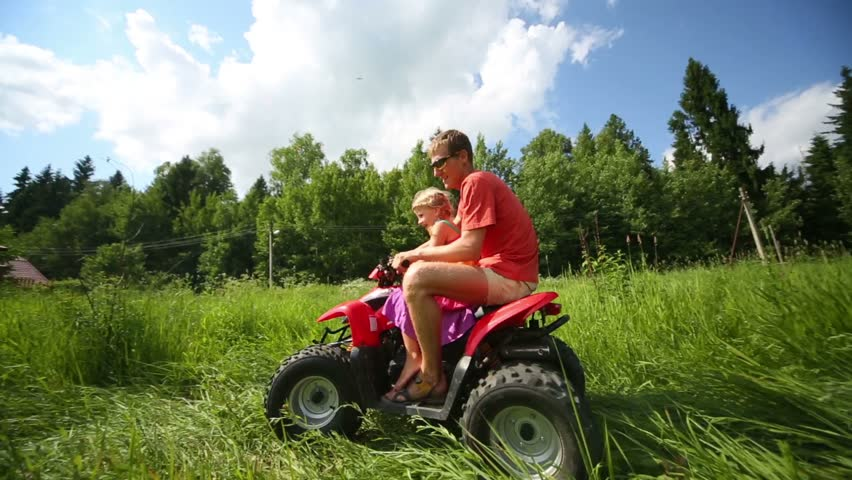Young father with little daughter rides around circle on ATV at green grass in summer day | Shutterstock HD Video #6486725