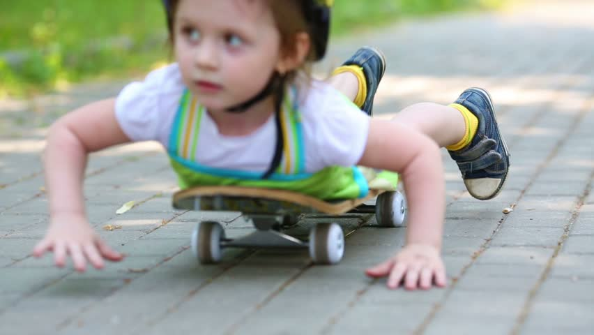 Girl goes in reverse lying on a skateboard at park