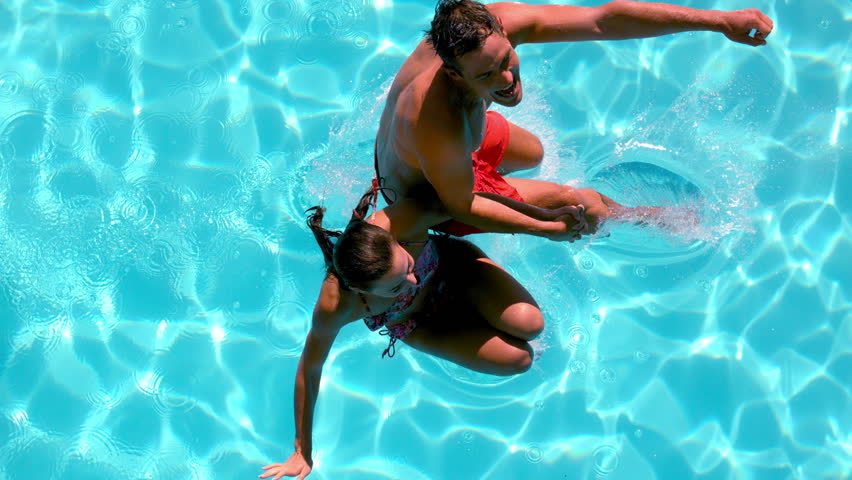 Couple holding hands and jumping in the swimming pool in slow motion - HD stock footage clip